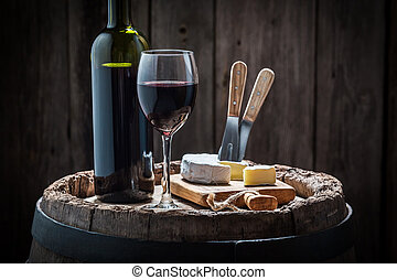 Red wine with camembert cheese on old barrel