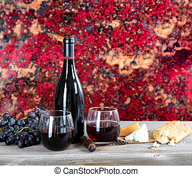 Red wine with fresh cheese and baked bread on rustic wooden table
