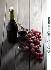 Red wine with grapes on wooden table