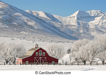 Large red barn in winter snow with tall snow covered mountains in the background.