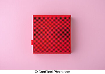 Red wireless speaker on pink background