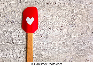 Red with heart kitchen spatula on wooden background