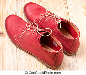 red women's leather shoes with laces on  wooden background