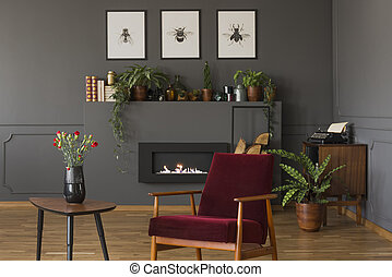 Red wooden armchair next to table with flowers in grey living room interior with posters. Real photo