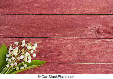 Red wooden background. Flowers lilies of the valley. Place for text.