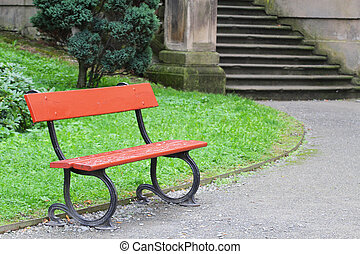 Red wooden bench with stairs in the background