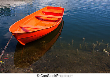 Red wooden boat on lake