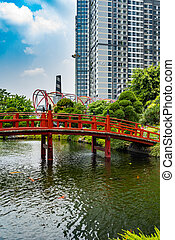 Red wooden bridge in Japanese garden at outside of residential complex building