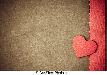 Red wooden decorative heart on beige cloth background.