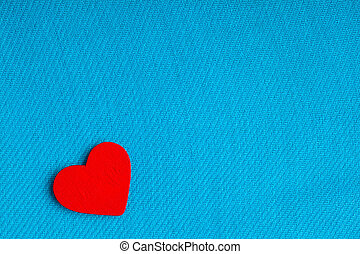 Red wooden decorative heart on blue cloth background.