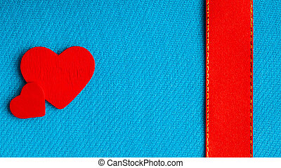 Red wooden decorative hearts on blue cloth background.