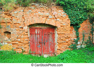 Red wooden door to an old wine cellar
