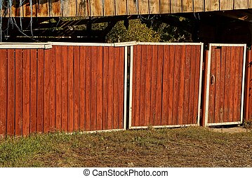 red wooden fence with gate and wicket outside in the grass