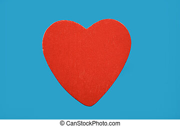 Red wooden heart isolated on blue background
