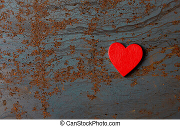 Red wooden heart on a metal background with copy space