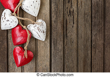 Red wooden hearts on old brown wooden background