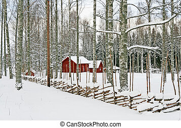 Red wooden houses in a snowy landscape - Traditional Swedish...
