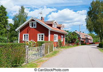 Red wooden houses in Sweden - Main street in Pataholm, a ...