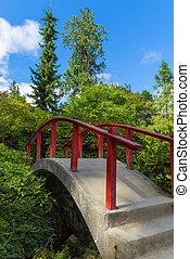 Red wooden Japanese foot bridge add theme to garden