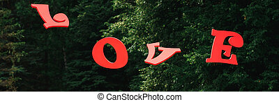red wooden letters love on the background of the forest