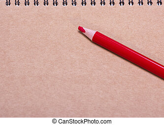 red wooden pencil on a brown sheet of paper