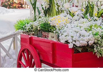 red wooden wheelbarrow with wooden boxes full of blooming artificial flowers. Street and garden decoration.