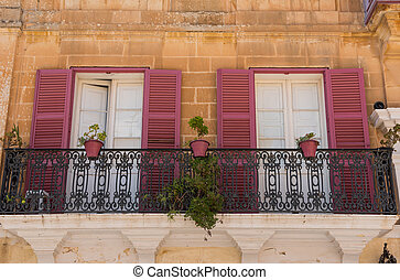 Red wooden window shutters on a house