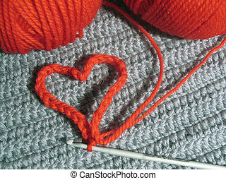 Red wool clews and knitted heart jn grey