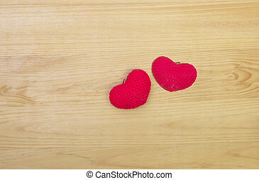 Red wool heart shape on wooden background