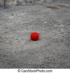 red woolen ball lies on the gray asphalt