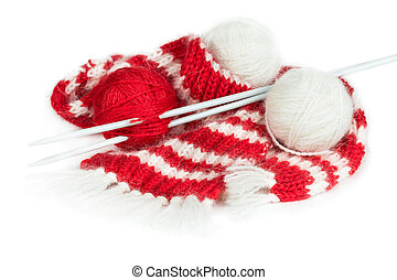 Red woolen scarf, knitting needles and balls of yarn