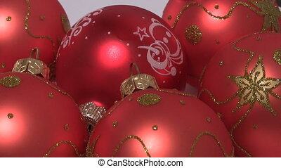 Red xmas baubles on white turning close-up