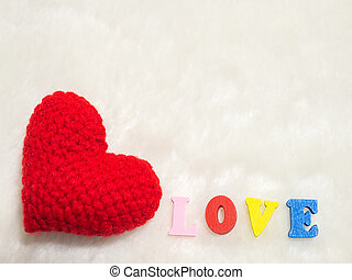 red yarn heart on white wool and alphabet LOVE. the red heart on the left of picture and background copy space for text. Valentines day, love concept and love background