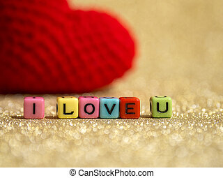 Red yarn heart with I Love You text from bead colorful on the gold floor and background copy space for text. Valentines day, love concept and love background