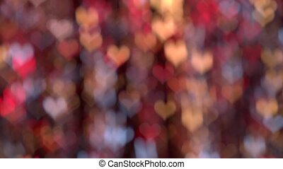 Red, yellow and blue bokeh lights heart shaped moving. Background lighting