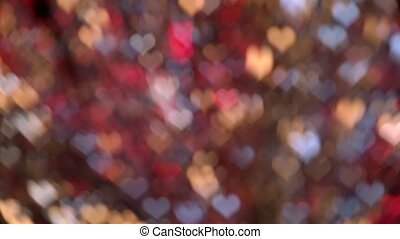 Red, yellow and blue gradient blurred background of bokeh heart shaped