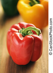 Red, yellow and green bell peppers on a wooden background.