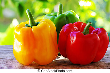 red, yellow and green pepper on table, green background
