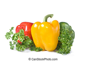 red, yellow and green pepper with parsley isolated on white
