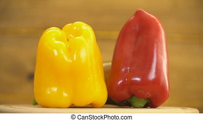 red, yellow and green peppers on a revolving wooden table