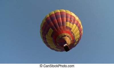 Red-yellow balloon flying in cloudless sky