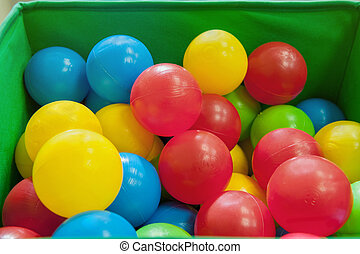 Red, yellow, blue plastic balls lie in the green box. The interior of the children's room with lots of colorful toys.