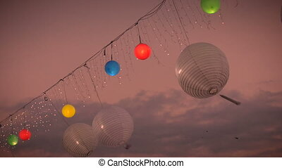 """Red, yellow, green, blue, and white paper lanterns blow in..."