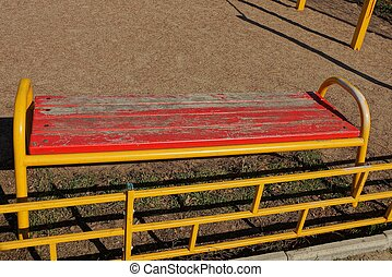 red yellow wooden dirty bench stands on brown sand