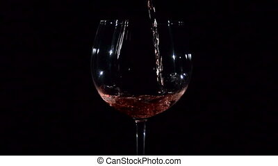 Red Young Wine Pouring into Glass on Black