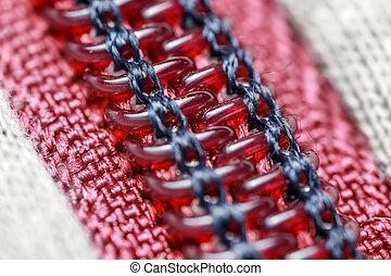 Red zipper fastener on white, close-up, macro,