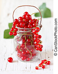 Fresh redcurrant berries in a glass jar on an old garden board.