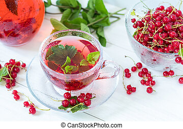Redcurrant drink in transparent glass carafe and cup. Clear...