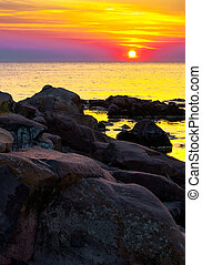 reddish sunrise over the sea with rocky shore. beautiful...