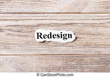 REDESIGN of the word on paper. concept. Words of REDESIGN on a wooden background
